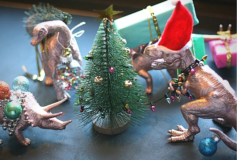 The dinosaurs for our dinosaur Advent wreath: Triceratops with baubles and garlands, Brachiosaurus with a tree, Stegosaurus with the presents and T-Rex tangled in the Christmas lights