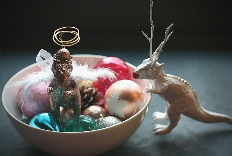 Simple dinosaur Christmas decoration ideas: Angelsaur in a bowl of Christmas ornaments with Reindino looking over the side
