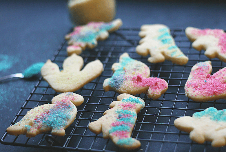 Delicious festive dinosaur sugar cookies with homemade edible glitter (in background), cooling on a wire rack