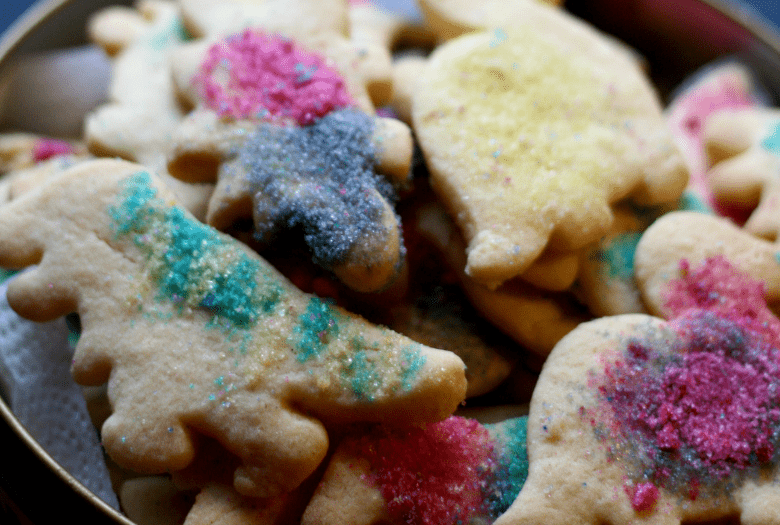 Close up of festive dinosaur sugar cookies in a cookie tin