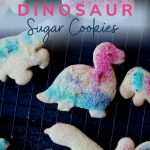Festive dinosaur sugar cookies: pin showing festive dinosaur sugar biscuits with homemade edible glitter, cooling on a wire rack