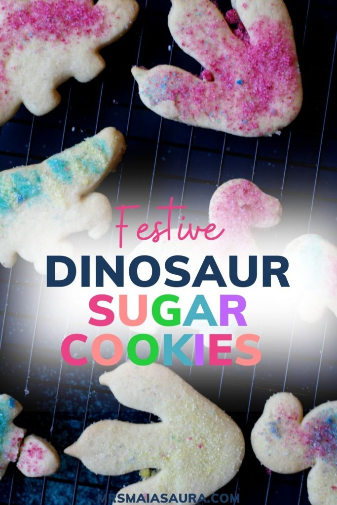 Pin: Festive dinosaur sugar cookies, with rack of fresh cookies cooling and text centre