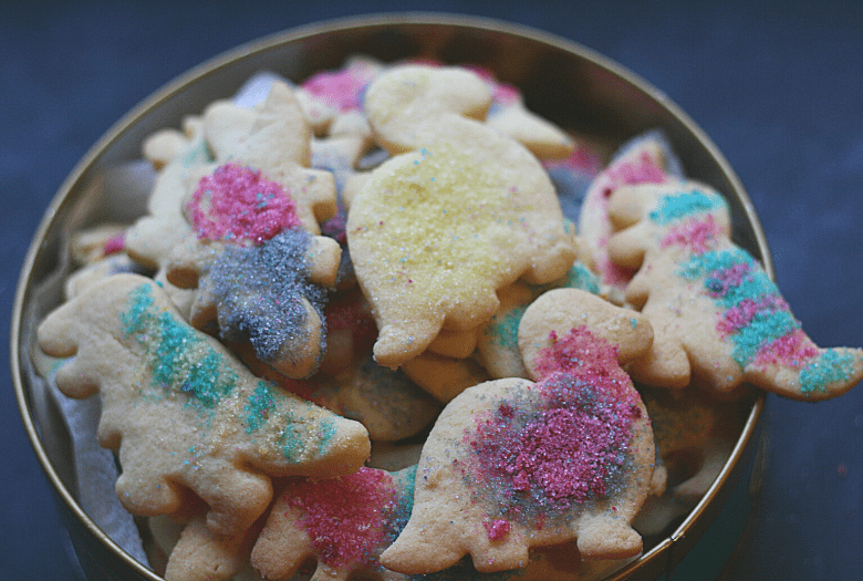 Biscuit tin filled with festive dinosaur sugar cookies with homemade edible glitter