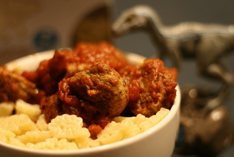 Meteorite Meatballs, served with marinara sauce and dinosaur pasta. With a toy Velociraptor looking on