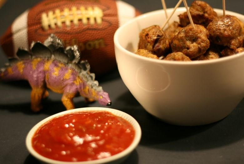 Game Day Snack: Meteorite Meatballs in a bowl with a bowl of salsa, a football and a toy Stegosaurus