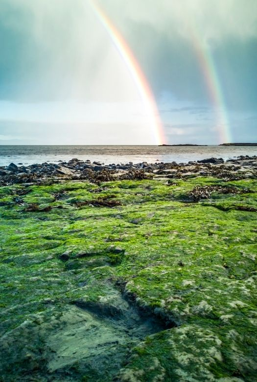 Rainbows over the dinosaur footprints at An Corran beach, one of the best places to see real dinosaur tracks in Europe