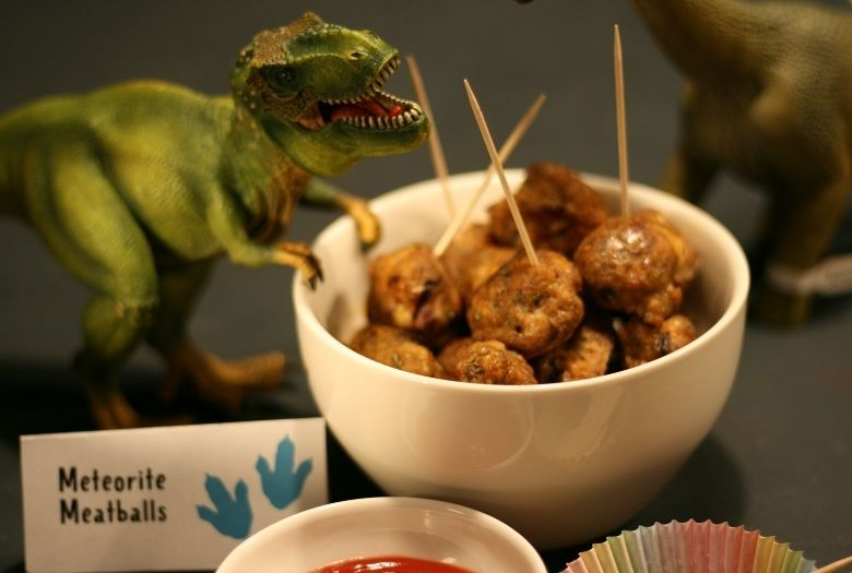 Dinosaur-themed birthday party: Meteorite Meatballs in a bowl with a bowl of ketchup, a Meteorite Meatballs sign and a hungry looking toy T-Rex
