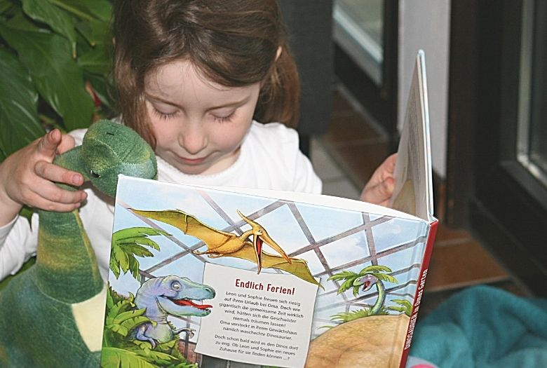 """Our LDA reading """"Dinosaurs in Grandma's Garden"""" (in German) to her Brontosaurus, just one of the fun dinosaur books to read aloud to your little dinosaur fan."""
