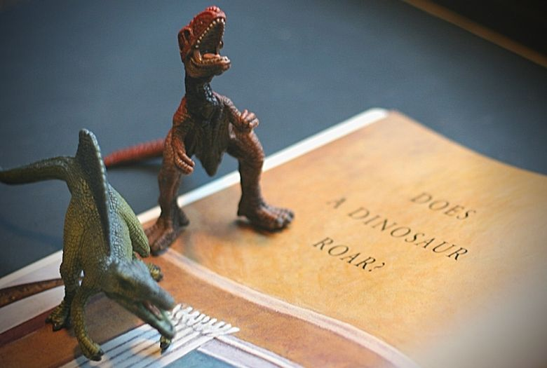 """Toy dinosaurs reading """"How Do Dinosaurs Say Goodnight?"""", one of our recommendations for fun dinosaur books to read aloud."""