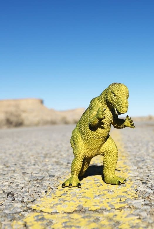 7 best dinosaur games for road trips, with an image of a toy dinosaur on a road