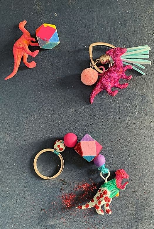 Cute dinosaur keyring with a brightly painted Pachycephalosaurs keyring with beads and a pink glitter parasaurolophus with a tassel.